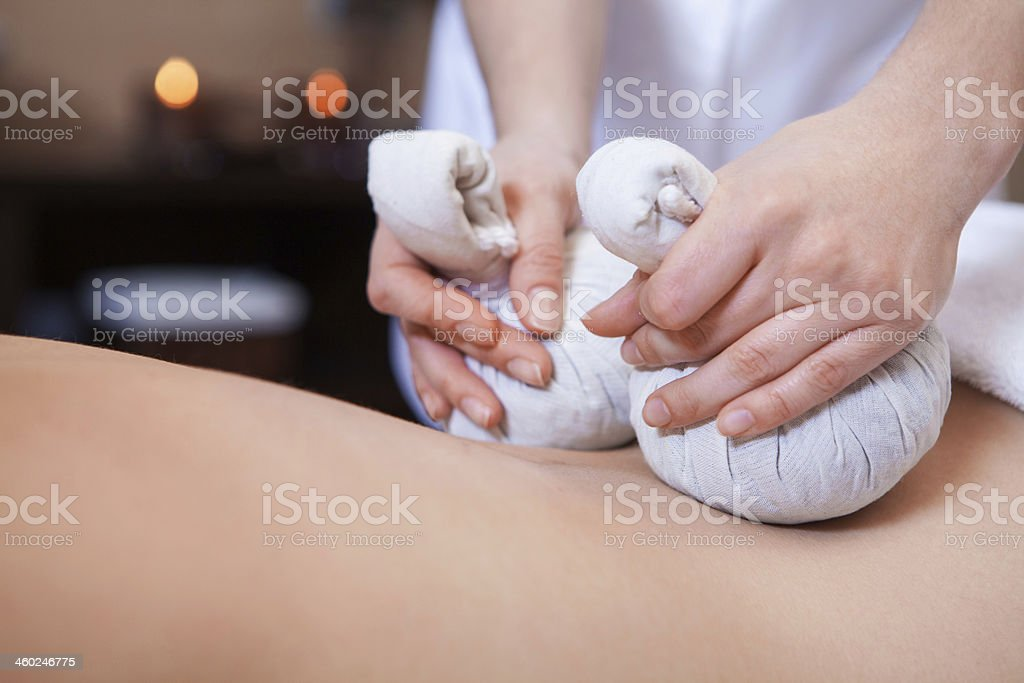 A pair of hands using Thai massage balls to relax someone stock photo