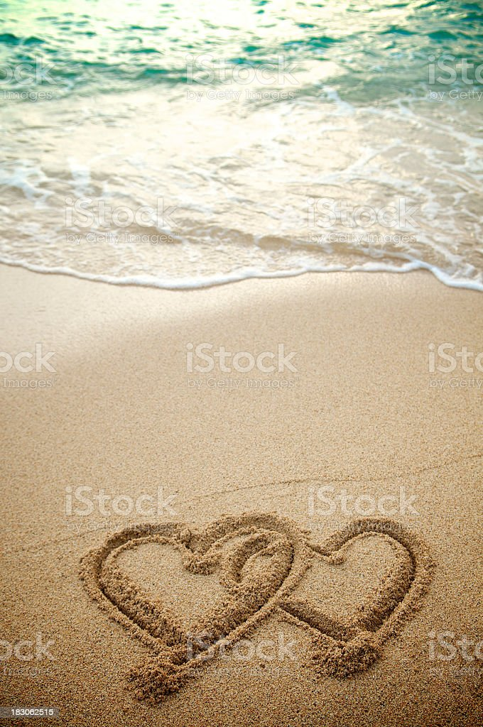 Pair of Hearts Intertwined on Beach w Turquoise Waves royalty-free stock photo