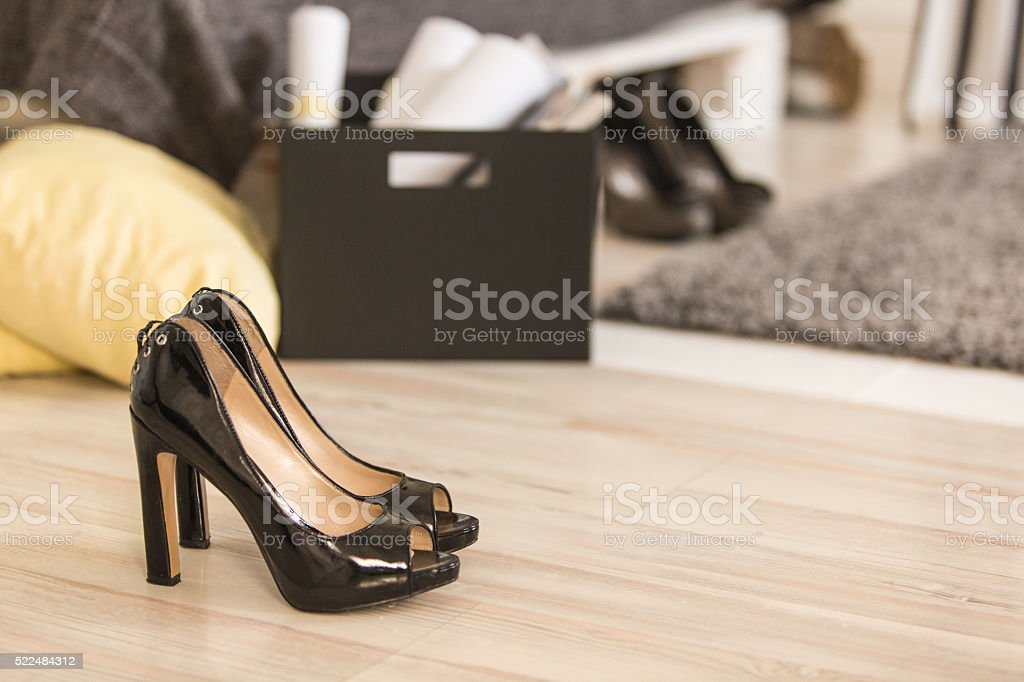 Pair of high heeled shoes on wooden floor stock photo