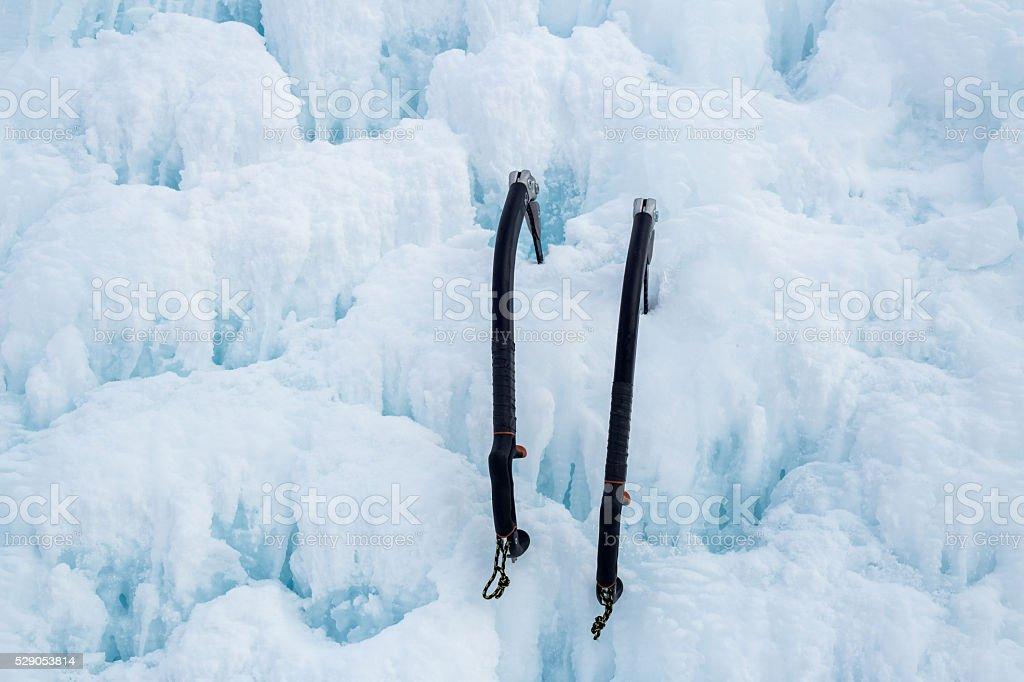 Pair of ice axes on blue wavy ice stock photo