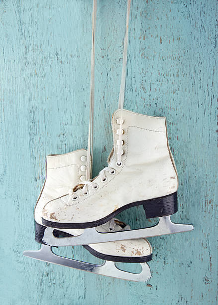 Pair of  ice skates on blue wooden background stock photo