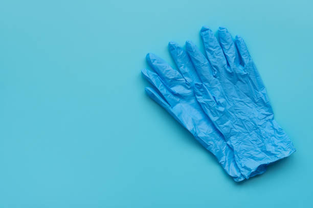 Pair of latex medical gloves ob blue background. Protection concept Pair of latex medical gloves ob blue background. Protection concept surgical glove stock pictures, royalty-free photos & images