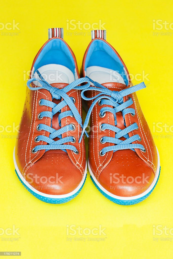 Pair of leather orange shoes with blue sholaces, copy space royalty-free stock photo