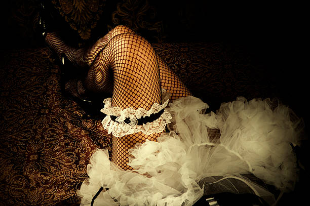 a pair of legs with fishnet stockings and a white garter - burlesque stock photos and pictures