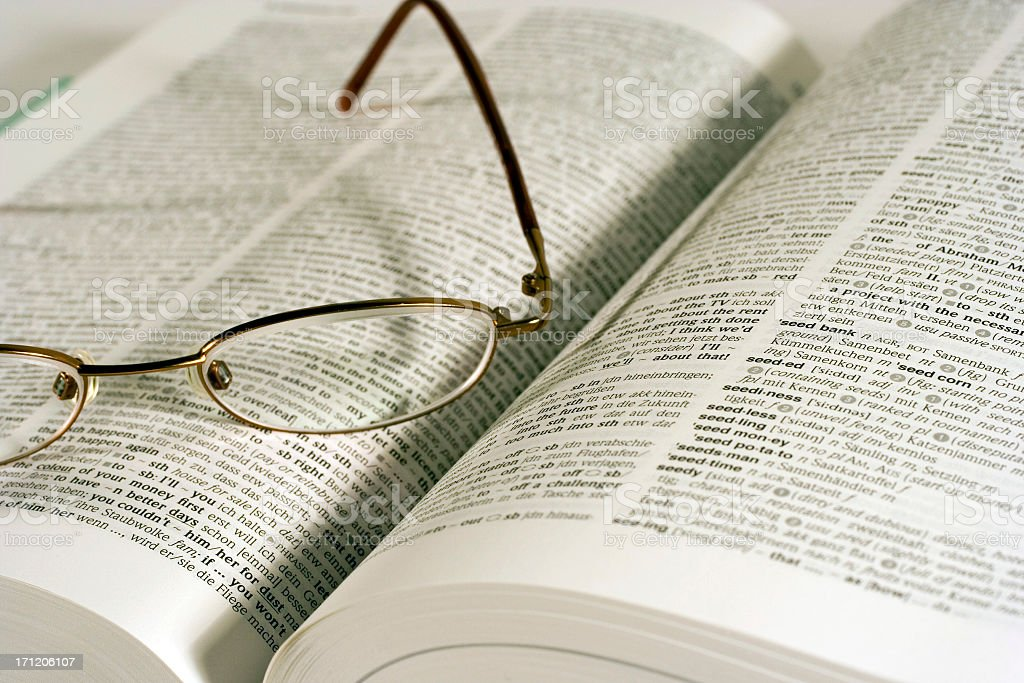 Pair of lightweight eyeglasses sitting on an open dictionary royalty-free stock photo