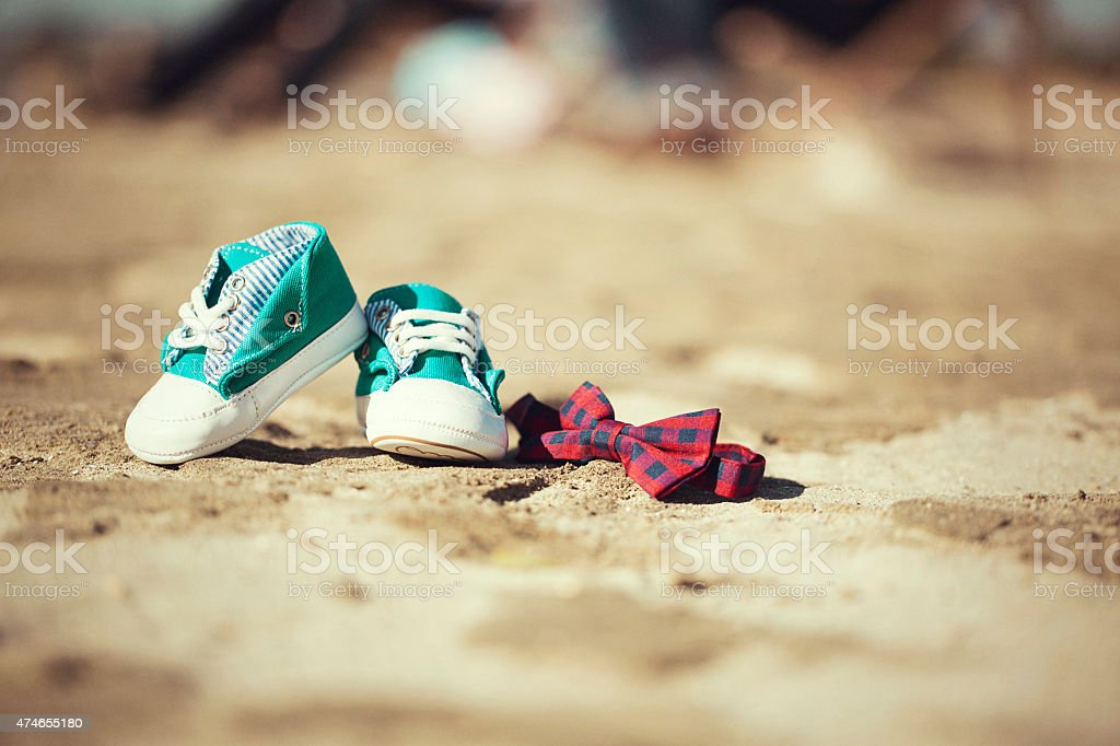Pair of little baby shoes with a bow tie stock photo