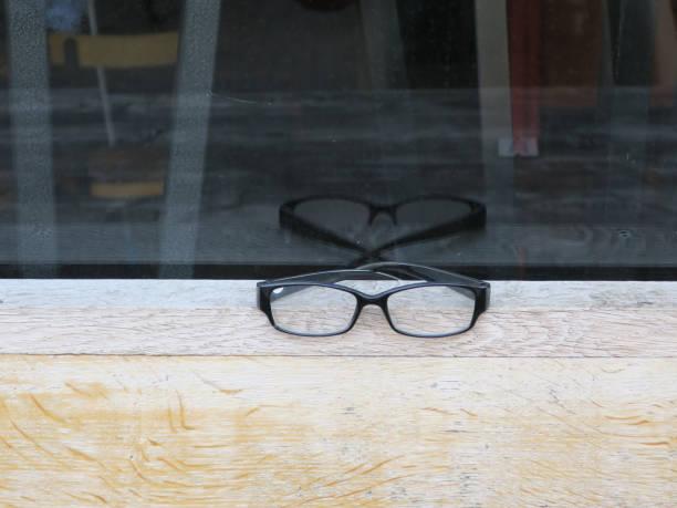 paar verloren lezingsglazen die op een houten vensterbank leggen foto