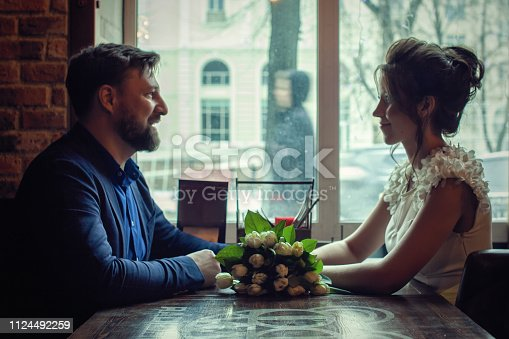 A pair of lovers sit in a cafe near the window.