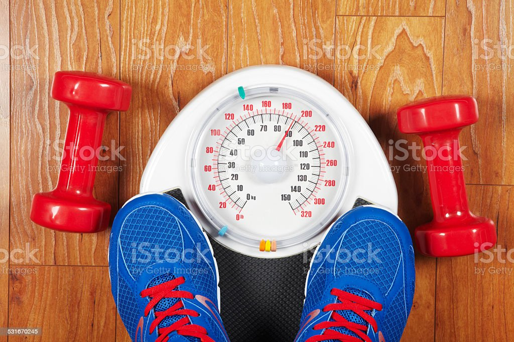 Pair of man's feet standing on a scale stock photo