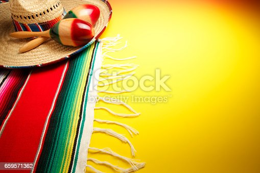 A still life of a pair of maracas on a sombrero and a multi-colored Mexican blanket that sits on a background that gradates from bright yellow to orange.