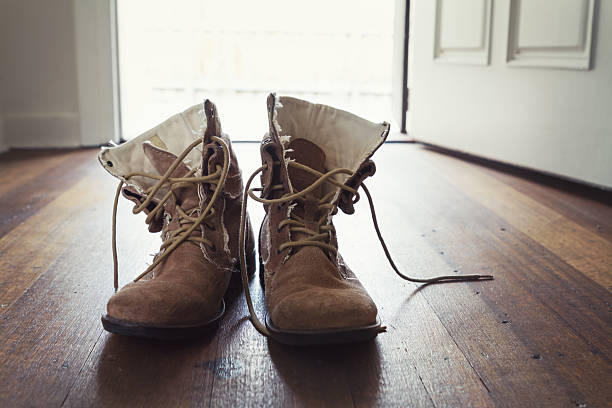 pair of men's worn leather boots in doorway of home - dirty shoes stock photos and pictures