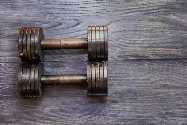 Pair of metal dumbbells on wood background stock photo
