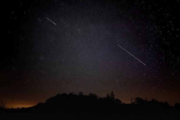 Pair of Meteors. Meteor Shower Night Sky Landscape Silhouette stock photo