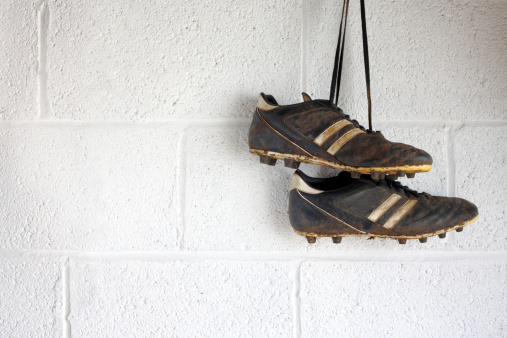 A pair of muddy black football boots hang up in a white-walled changing room. There is room for copyspace.