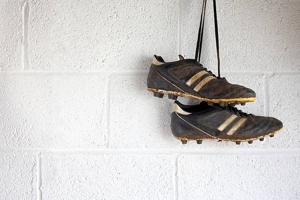 Pair of muddy black football boots A pair of muddy black football boots hang up in a white-walled changing room. There is room for copyspace. studded stock pictures, royalty-free photos & images