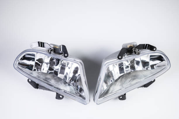 A pair of new embedded in the front bumper fog lights on a gray background. New modules of additional lighting spare parts for the car stock photo