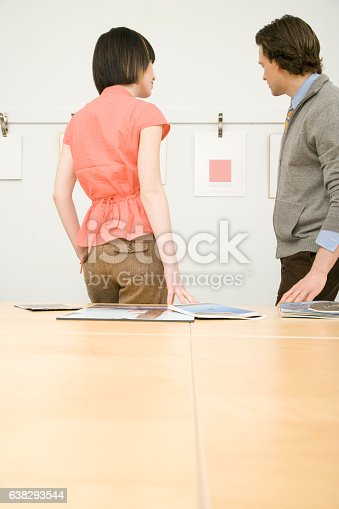 istock Pair of office colleagues looking at designs in meeting room 638293544