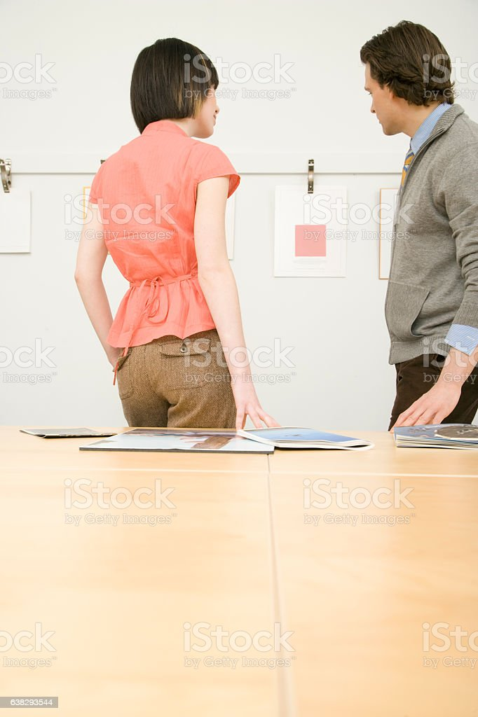 Pair of office colleagues looking at designs in meeting room stock photo