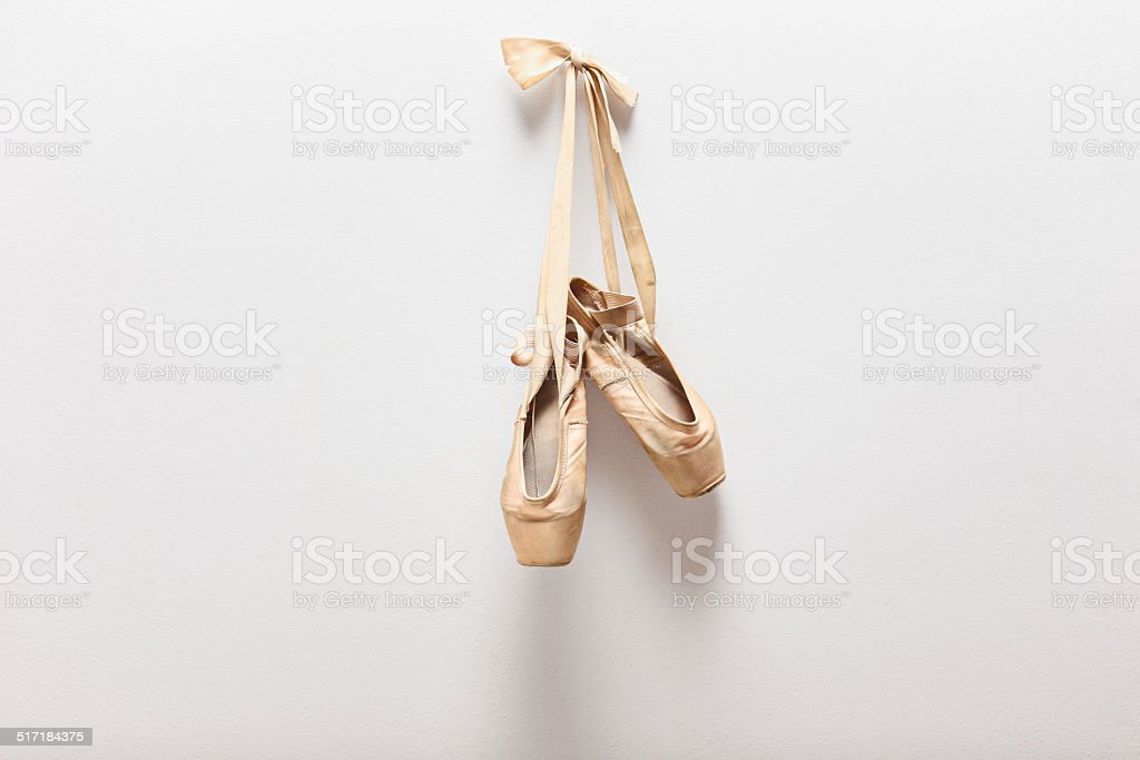 Pair of old ballet shoes hanging on a wall stock photo