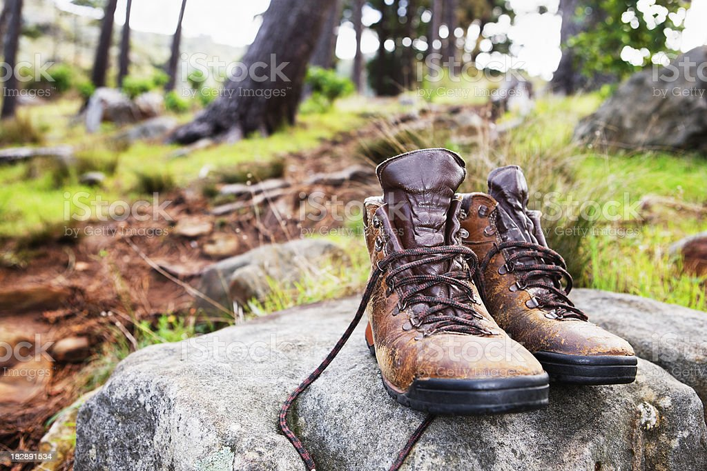 Pair of old hiking boots on a rock in woods royalty-free stock photo