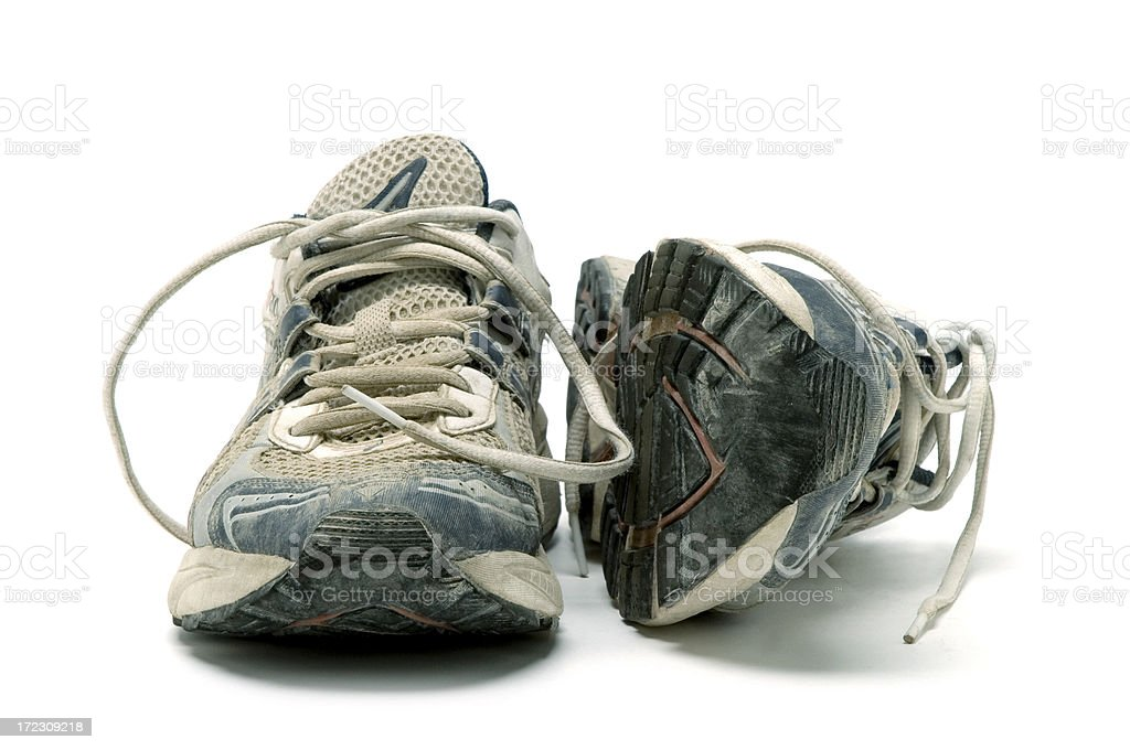 Pair of old used running shoes isolated on white background stock photo