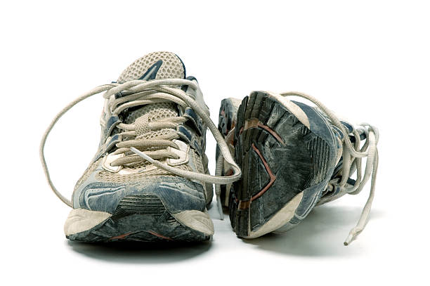 pair of old used running shoes isolated on white background - running shoes stockfoto's en -beelden