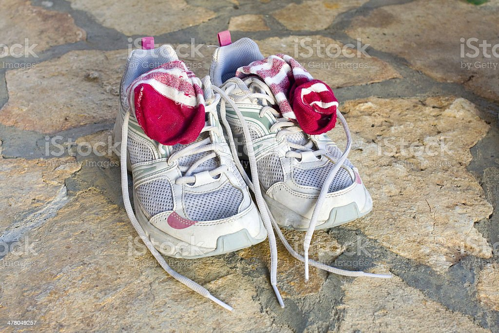 pair of old used running shoes with socks royalty-free stock photo