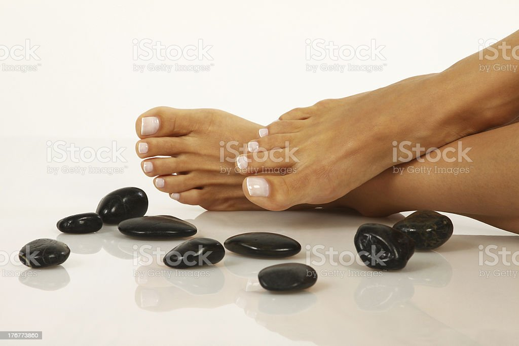 A pair of pedicured feet next to black pebbles stock photo