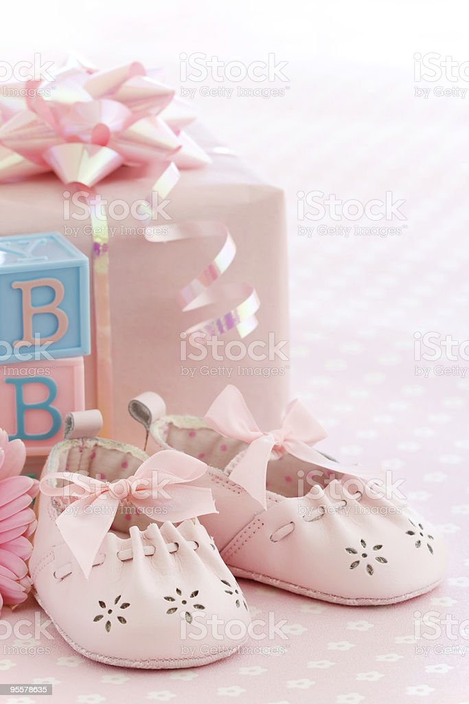 Pair of pink baby shoes in front of a pink present stock photo