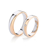 Pair of pink gold and silver wedding rings isolated on white background. Female ring decorated with diamond. Silver and gold wedding ring bands