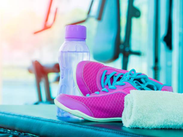par de deporte rosa zapatos de botella de agua de la toalla en la sala de fitness con fondo de equipos de fitness. - set deportivo fotografías e imágenes de stock