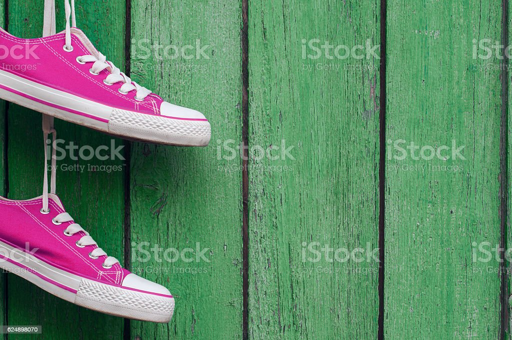 pair of pink sports sneakers hanging on a wooden wall stock photo