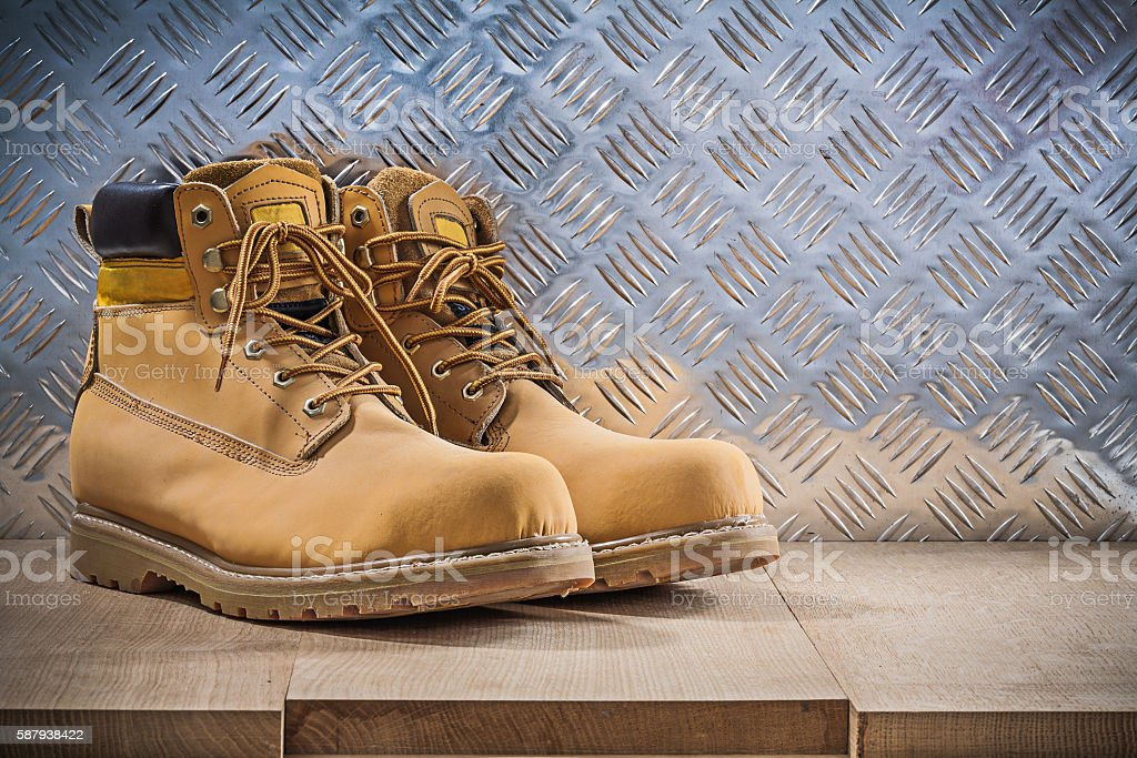 Pair of protective waterproof boots wooden board grooved metal s stock photo