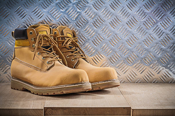 Pair of protective waterproof boots wooden board grooved metal s Pair of protective waterproof boots wooden board grooved metal sheet construction concept. boot stock pictures, royalty-free photos & images