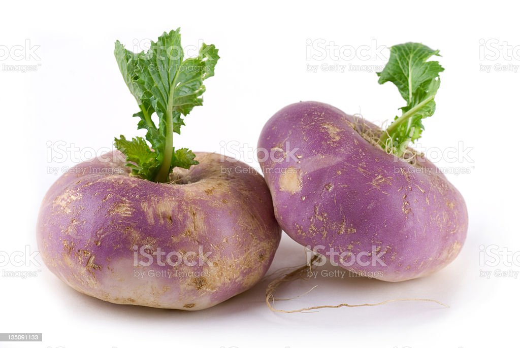 Pair of purple turnips with green leaves stock photo