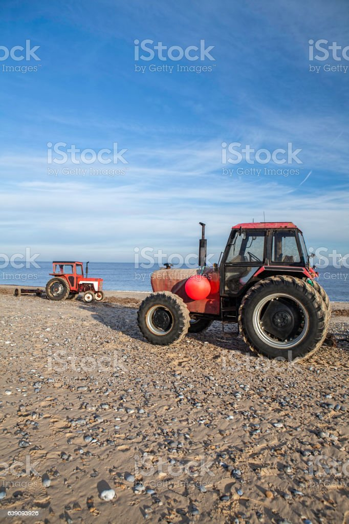Pair of red beach tractors ready for environmental clean-up stock photo