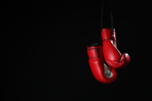 Pair of red boxing gloves hanging on black background, space for text