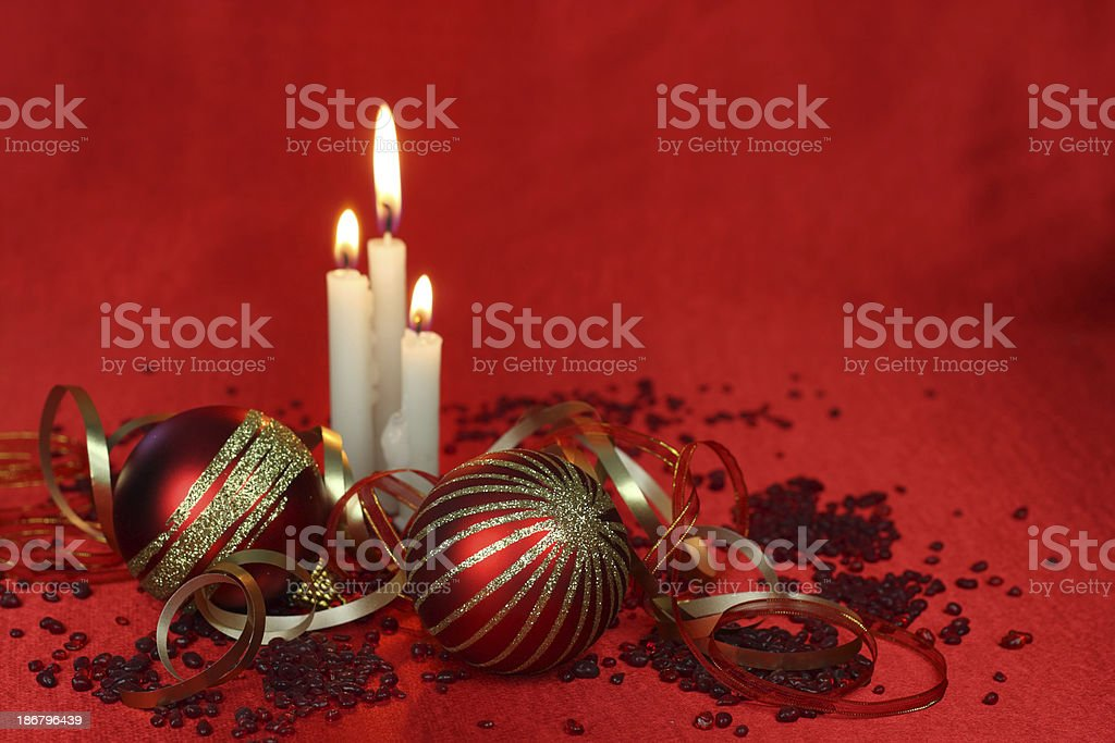 Pair of red Christmas baubles and gold glitter with candles royalty-free stock photo