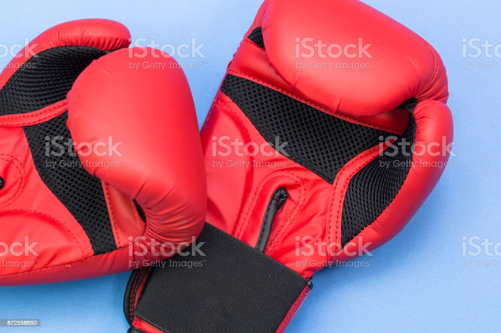 Pair of red leather boxing gloves isolated on blue background stock photo