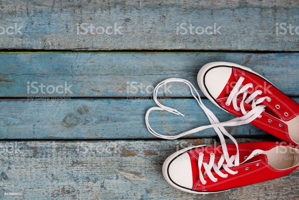 A pair of red retro sneakers on a blue wooden background, laces lined in a heart shape. Concept of young hipster love stock photo