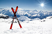 Pair of red skis crossed and wedged in snow on mountain