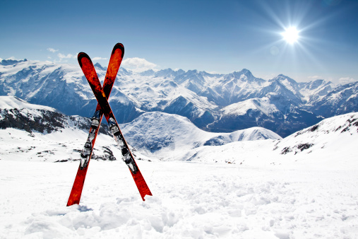 Pair Of Red Skis Crossed And Wedged In Snow On Mountain Stock Photo - Download Image Now