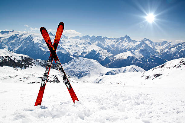 Pair of red skis crossed and wedged in snow on mountain​​​ foto