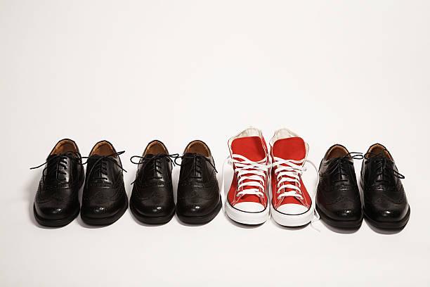 paar rote sneaker in einer reihe von schwarzen schuh - individualität stock-fotos und bilder
