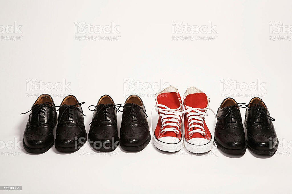 Pair of red sneakers in a row of black dress shoes stock photo