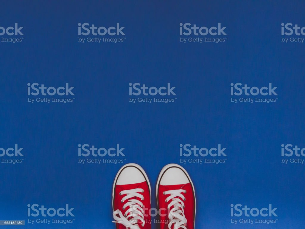 Pair of red sneakers on the blue pastel background. stock photo