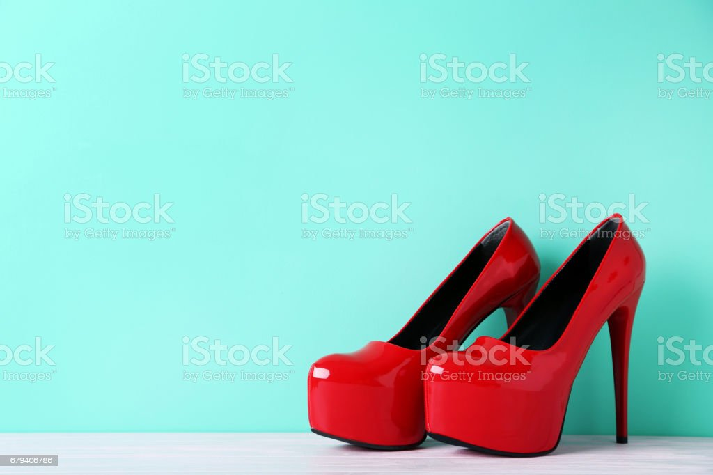 Pair of red women's high-heeled shoes on wooden table royalty-free stock photo