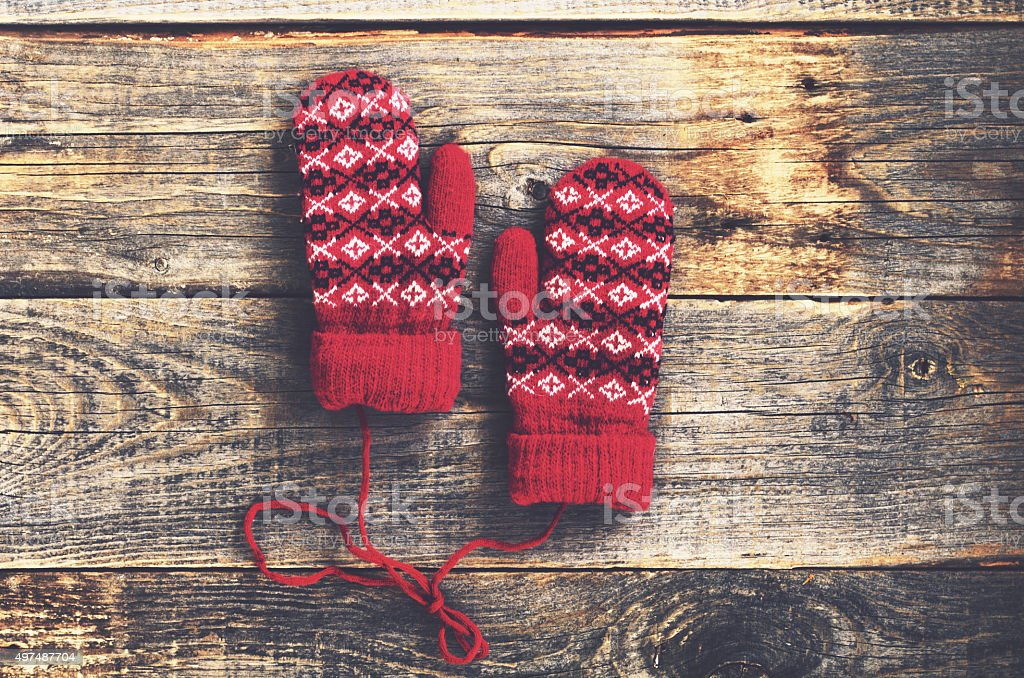 Pair of red woolen mittens on wooden background stock photo