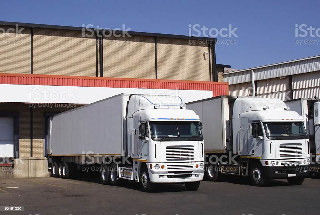 pair of refrigerated transporters at a food warehouse loading dock stock photo