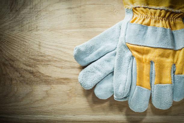 paar arbeitshandschuhe auf holzbrett - arbeitshandschuhe stock-fotos und bilder